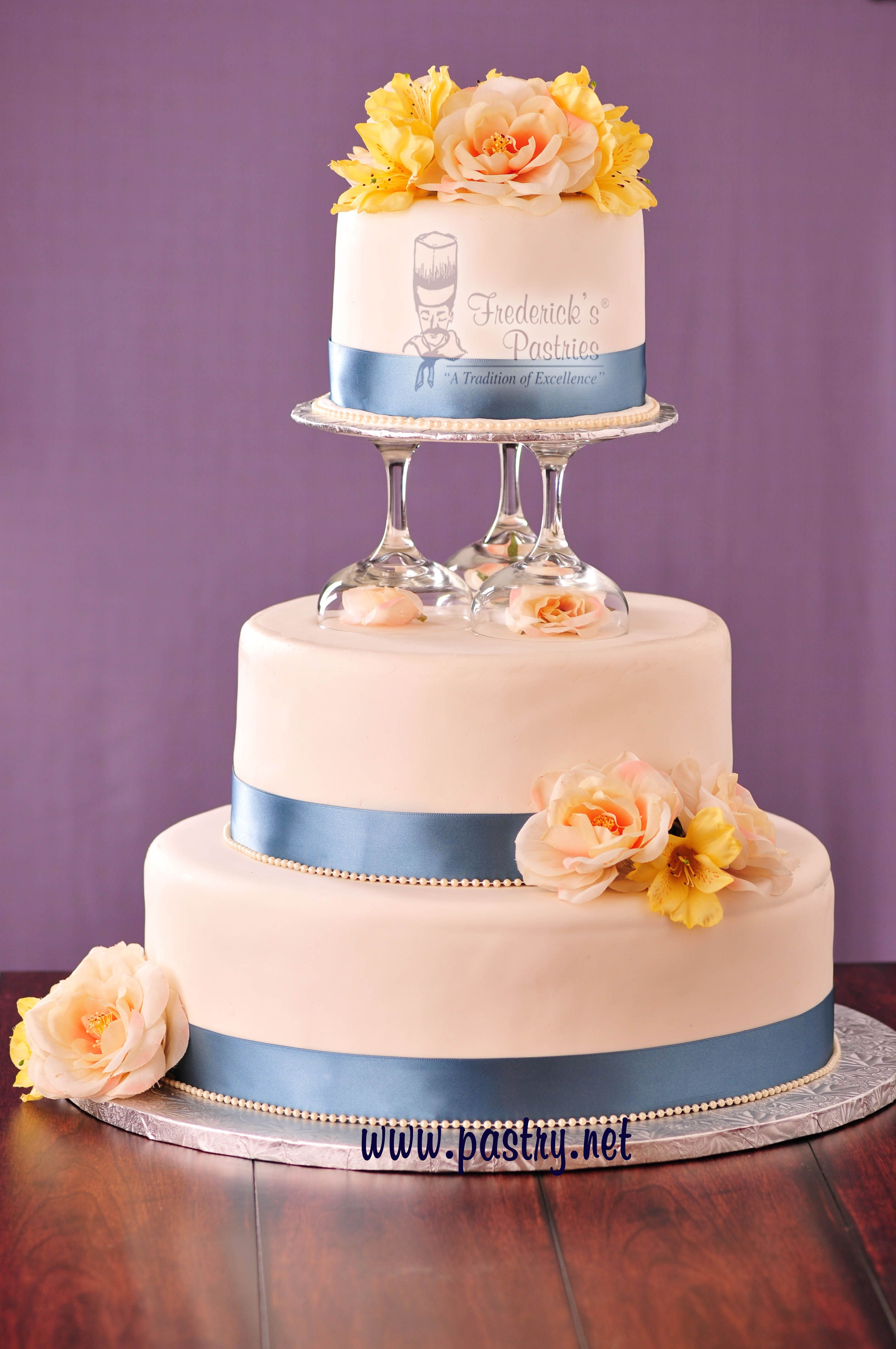 Light blue wedding cake with yellow and peach flowers. Frederick's Pastries #weddingcakes