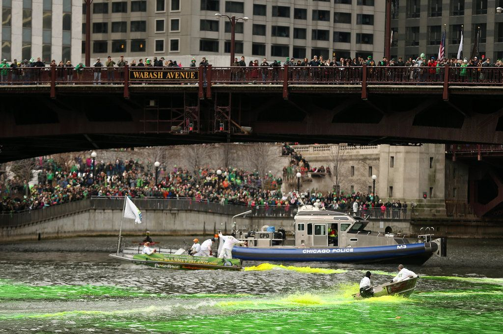 Crowd watches as members of the Chicago Journeymen Plumbers Local Union 130 pour green dye into the Chicago River for St Patrick's' Day
