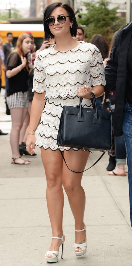 Demi Lovato stepped out in a summer-ready matching set—white lace scalloped pieces—that she coupled with aviators, a black top-handle tote, and white platform sandals.