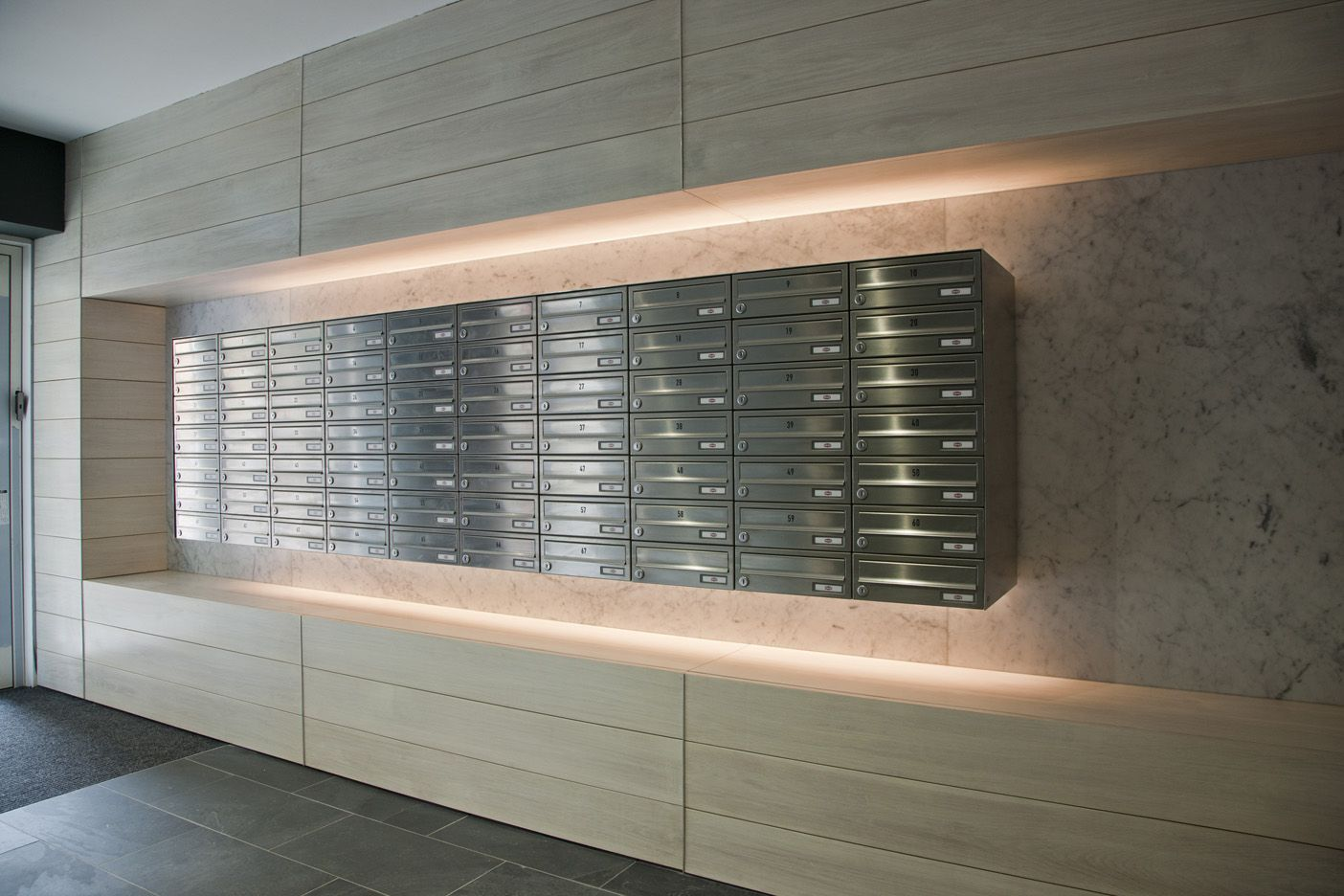 A bank of high-end horizontal stainless steel mailboxes ...