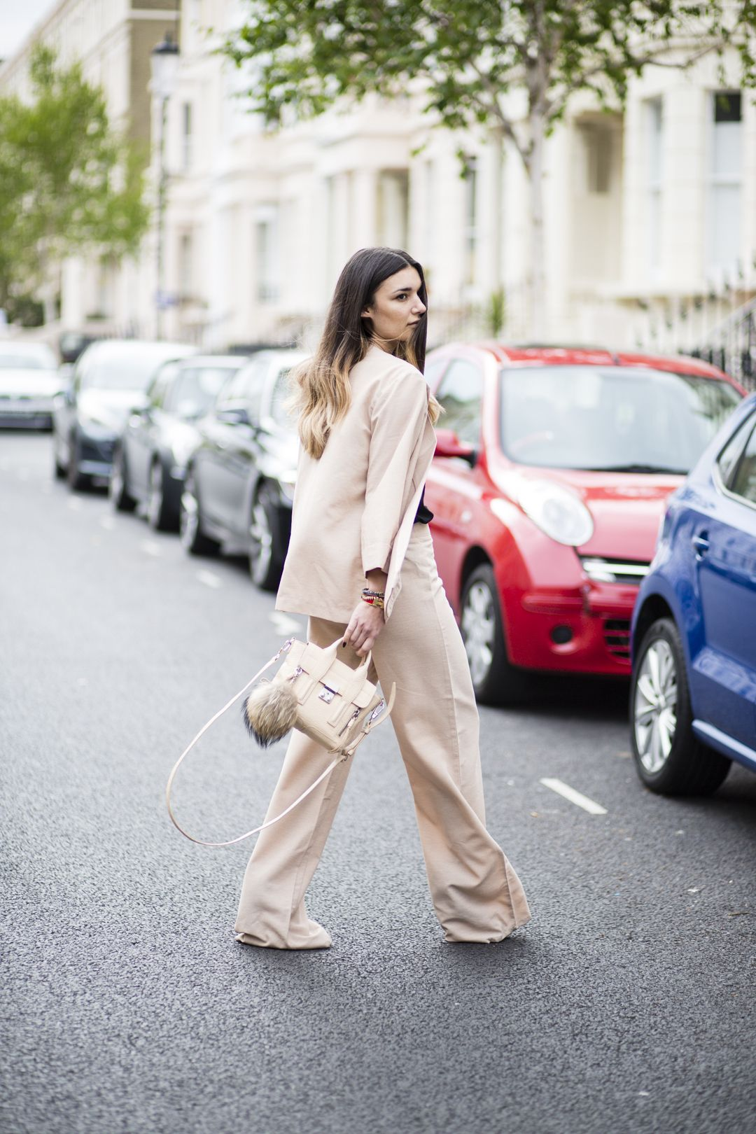 Anisa Sojka wearing beige Fashionnoiz wide-leg pant suit, black H&M cami top, Shashi stackable hippie bracelets and beige 3.1 Phillip Lim mini pashli cross-body bag. Fashion blogger streetstyle shot in London by Cristiana Malcica.