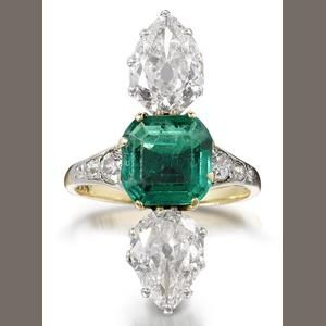 An emerald and diamond ring, first quarter of the 20th century  Set to the centre with a step-cut emerald, between two vertically aligned pear-shaped diamonds, weighing 1.59 and 1.51 carats, the shoulders decorated with graduating trios of old brilliant-cut diamonds.