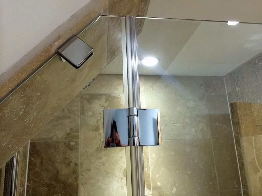 Angled made to measure semi-frameless inline shower door with angled fixed glass panel in a loft conversion by Room H2o. #LoftShowerDoors #AngledLoftShowers