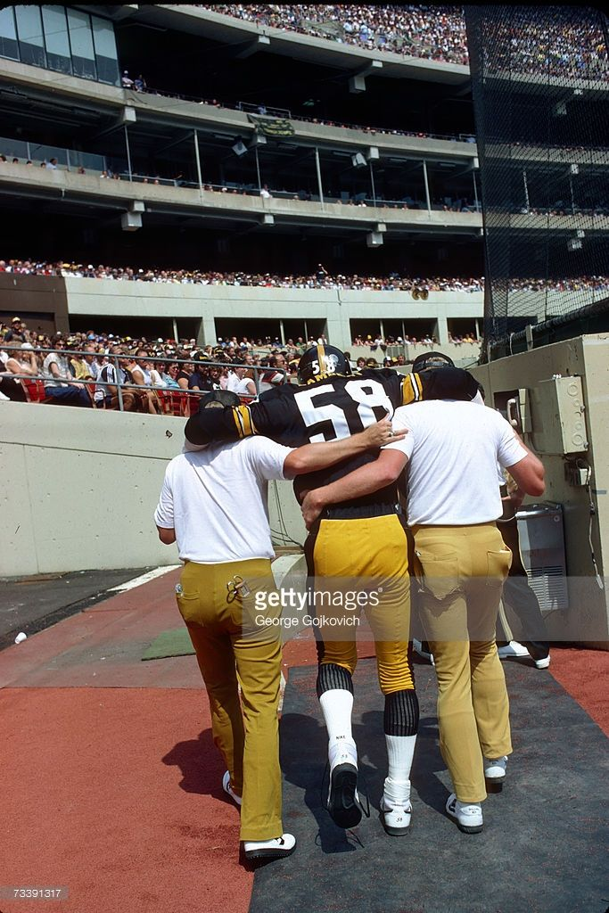Linebacker Jack Lambert #58 of the Pittsburgh Steelers is helped to the lockerroom after injuring his foot during a game against the Kansas City Chiefs at Three Rivers Stadium on September 2, 1984 in Pittsburgh, Pennsylvania.