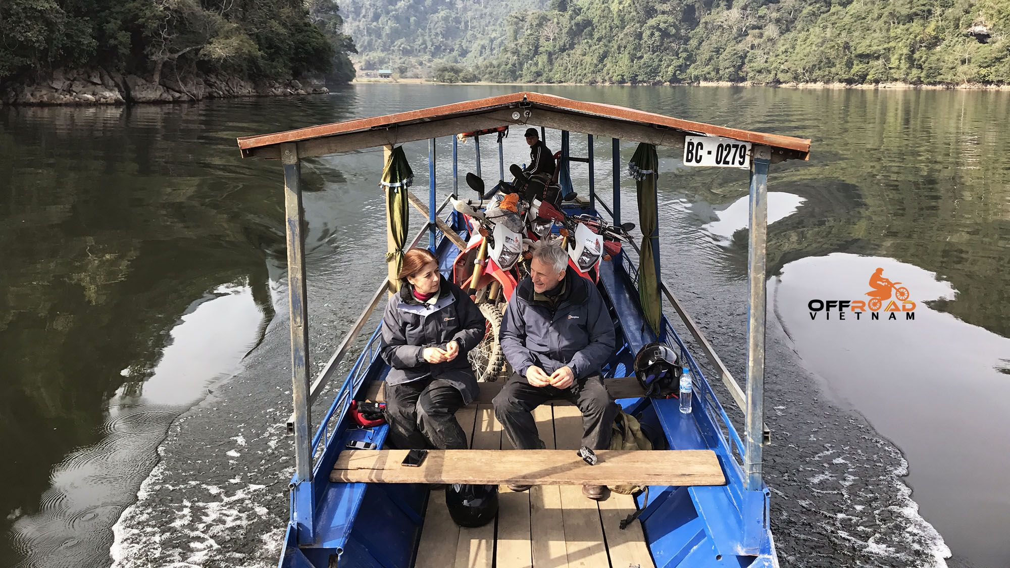 Crossing ba be lake by boat on a vietnam motorbike tour by