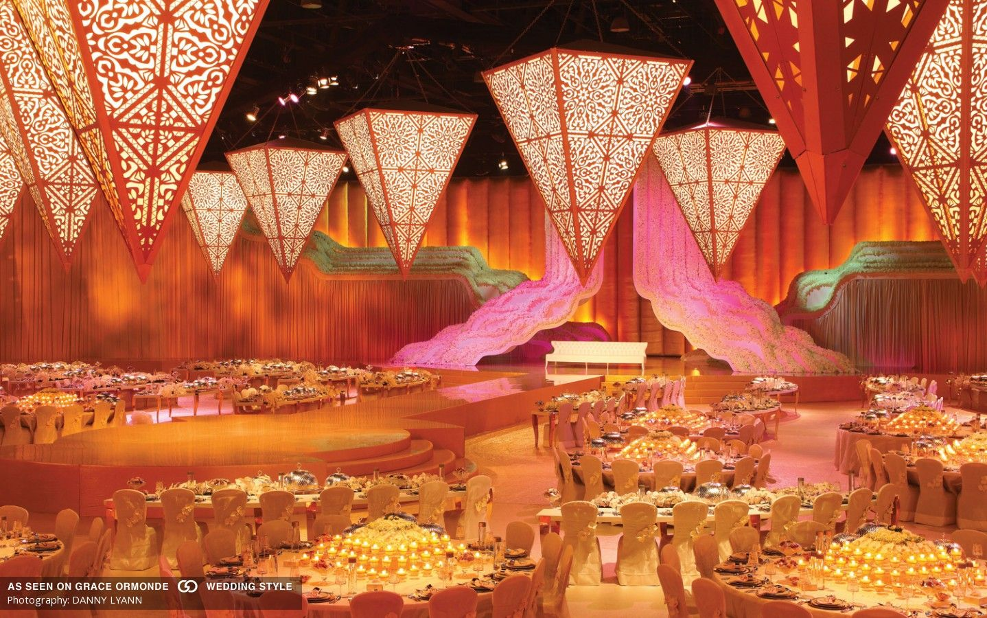 wedding stage decoration pics%0A Oversized lasercut lanterns  cascading waterfall of flowers on the stage   and tabletops featuring pyramids of candles and blossoms  except stage decor