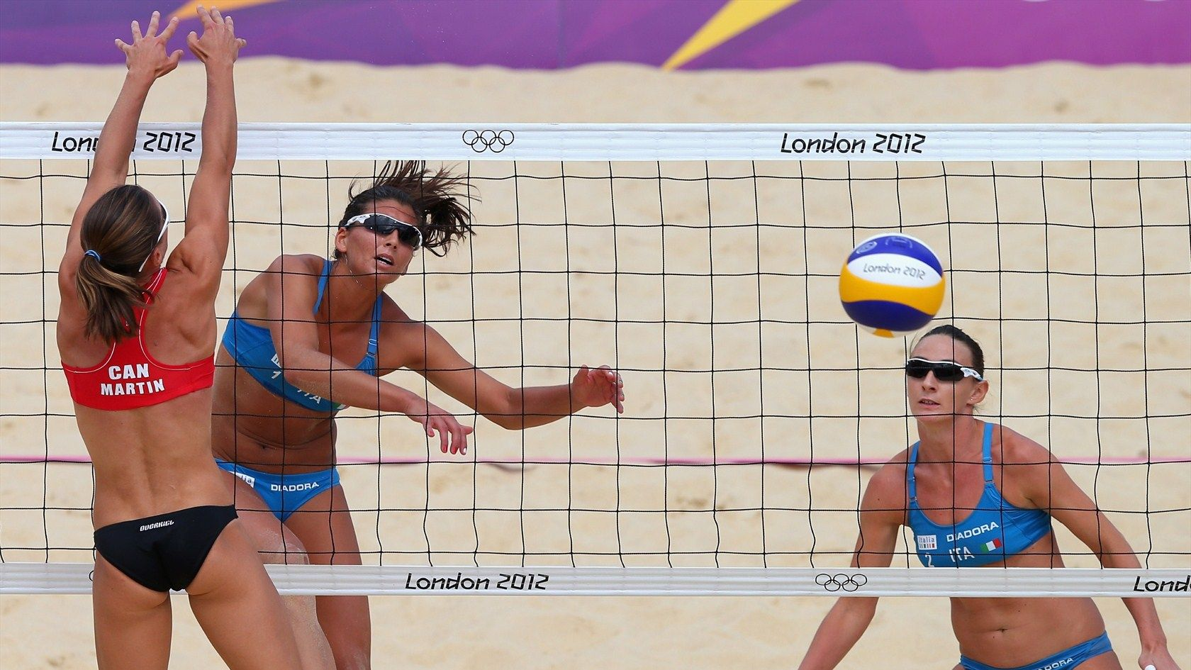 Italy S Marta Menegatti Hits Inside The Block Of Annie Martin Of Canada On Day 6 Of Olympic Competition The Italian S Won To Remain Undefeated Women S Beach V