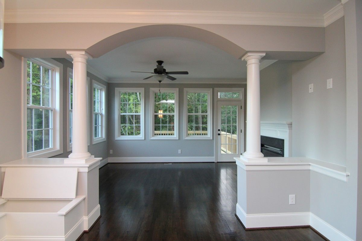 Beyond This Arched Entrance With Dual White Columns Is A Sun Room Two Sided Fireplace