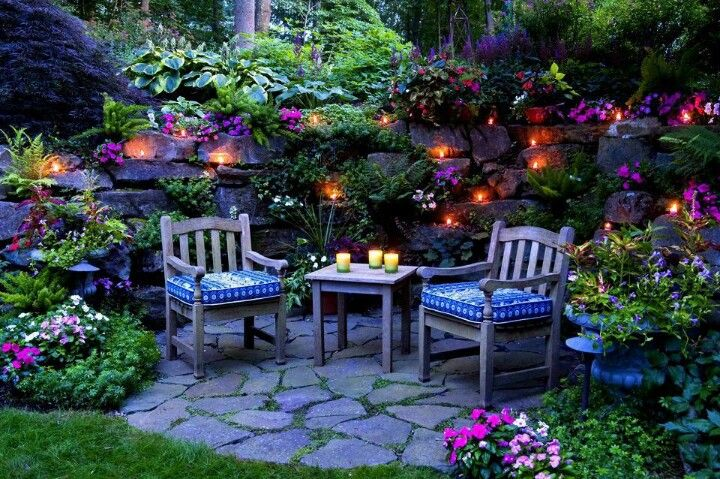 cozy outdoor space done with landscaping  flowers  landscape lighting and candles  perfect space