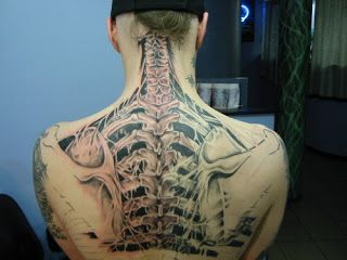 anatomical tattoo: the spine and the ribs are revealed under the ripped skin