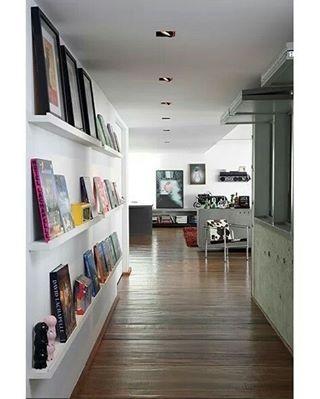 Você já pensou em decorar o corredor? Esse, mesmo ampliado na reforma, ganhou prateleiras estreitas para expor livros, quadros e objetos. Confira mais ideias em casaejardim.com.br #corredor #décor #decoração #decoraçãoétododia #decoration