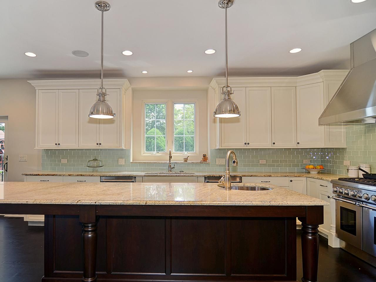 This kitchen has a soft blue glass tile backsplash with traditional