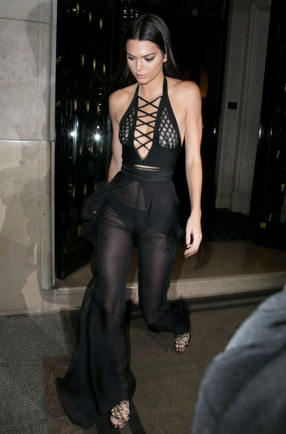 6f03e066c2ea Kendall Jenner wears a sheer lace-up halter top with sheer wide-leg pants by  Balmain and strappy sandals
