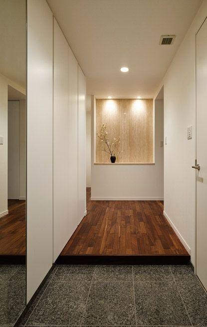 正面のニッチは 天板と壁を大理石のトラバーチンに変えて既存を活用 流れるような模様が上品な印象を与えます 床にはリビングと同じウォールナット 土間は既存の御影石 壁や収納の白さが個性的な 素材感を引き立てています 専門家 株式会社クラフトが手掛けた 玄関