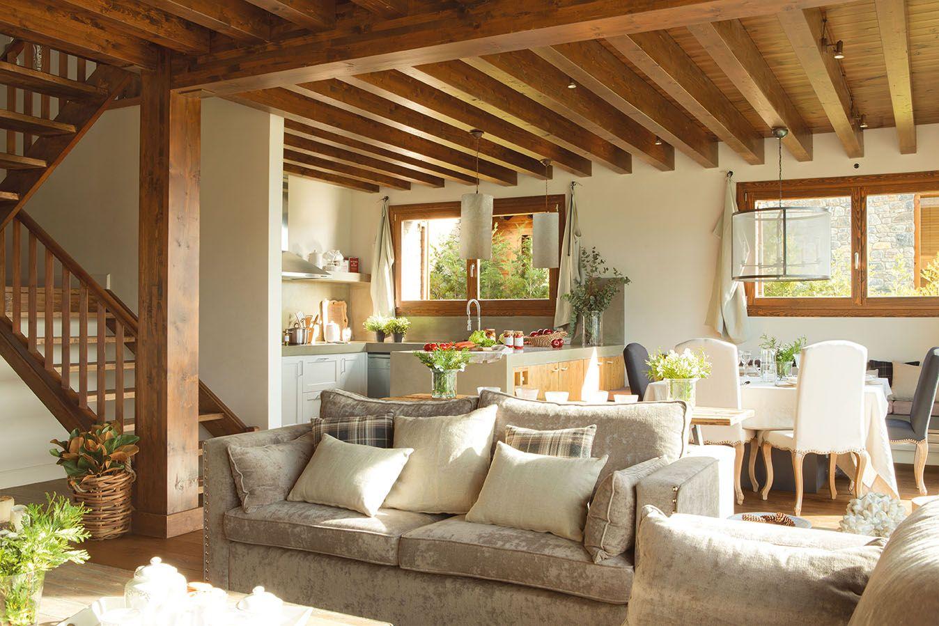 Salón y cocina con vigas en un mismo espacio con mobiliario en tonos ...
