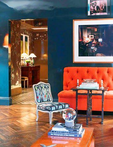 Un mur bleu canard mat et un canapé en velours orange