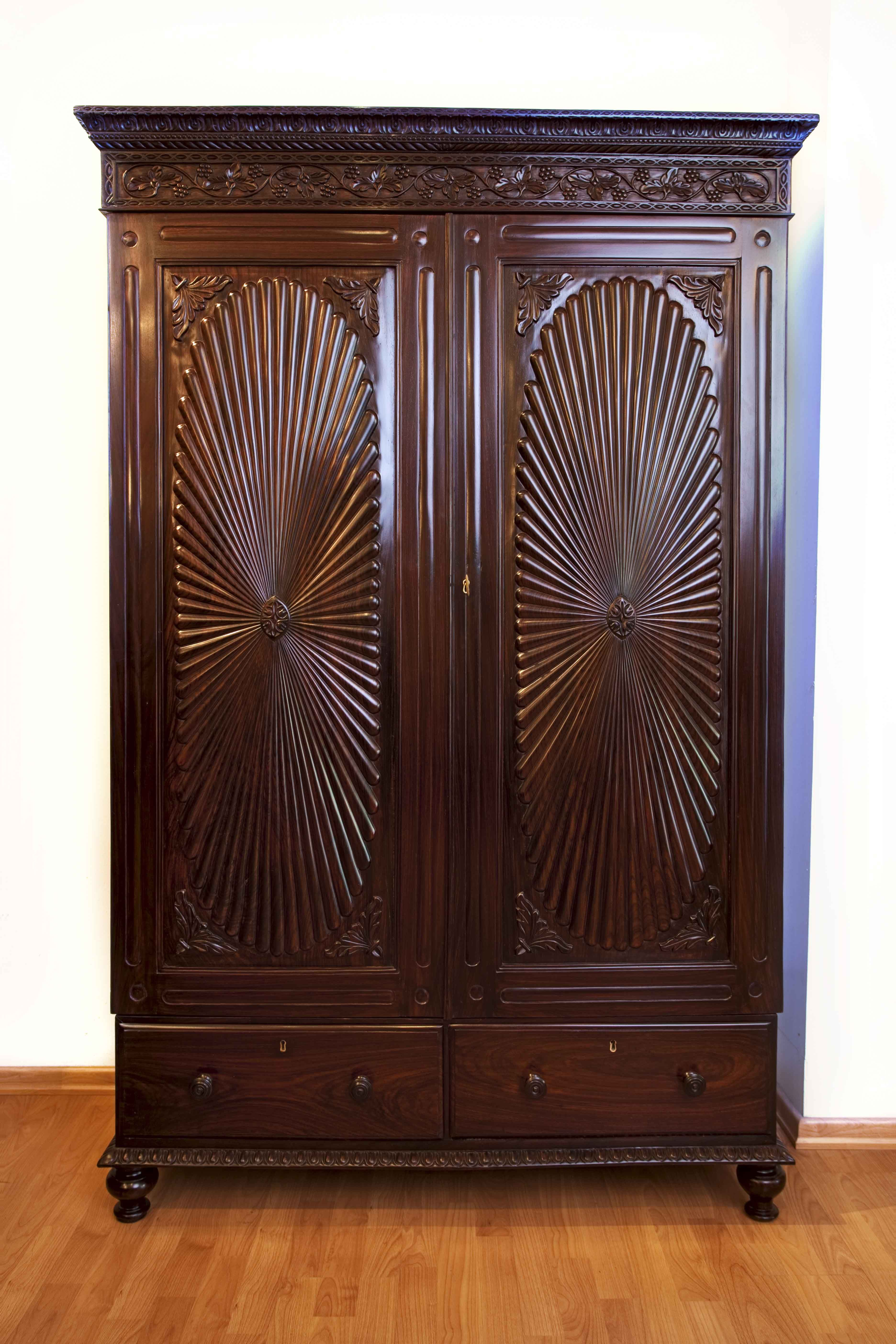 A British colonial rosewood cupboard with Fleur de Lys carving on