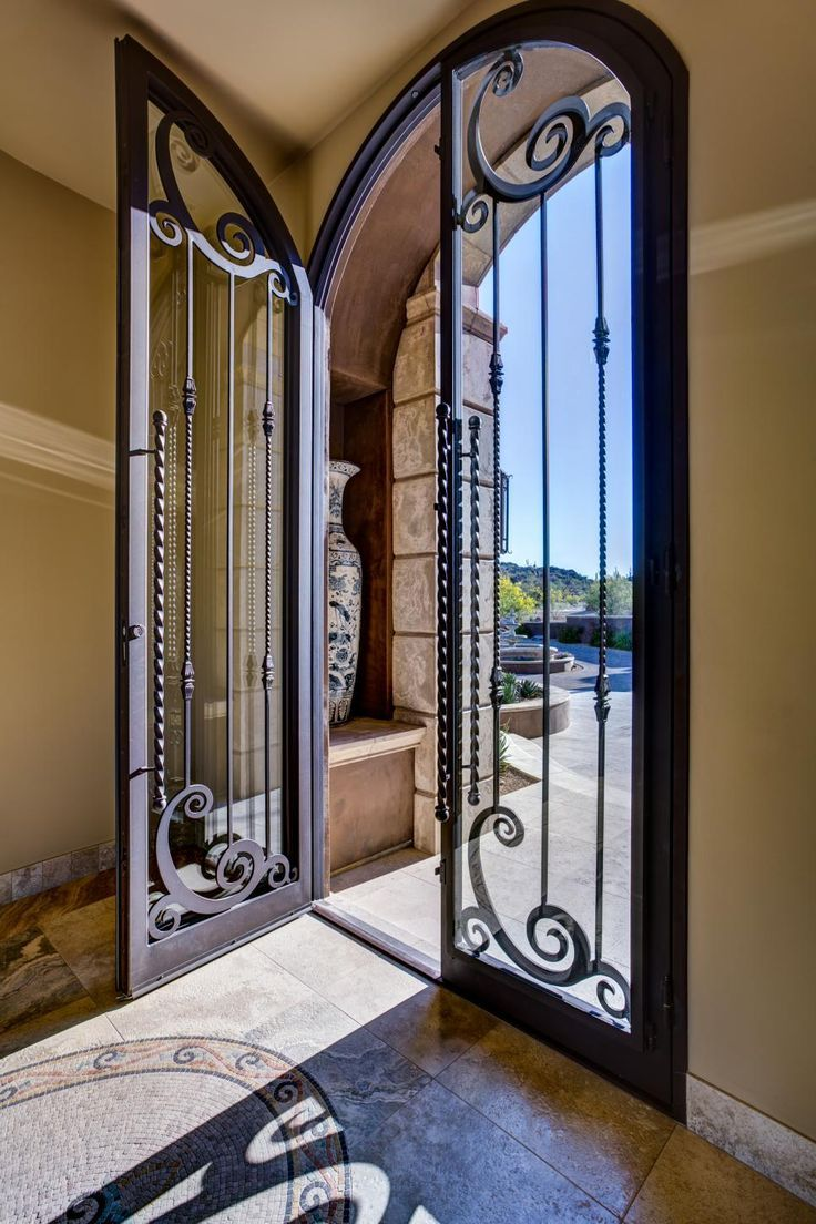 A Double Door Makes Commanding Statement That Draws The Eye Inward In This Mediterranean Inspired Home Light Pouring Through Gl Brings