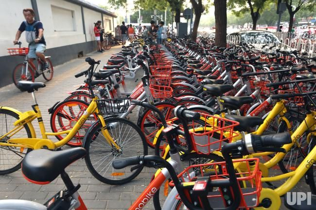A Chinese man rides past rows of Mobike (orange) and Ofo bike-sharing bikes on a sidewalk in Beijing on July 17, 2017. Bike-sharing giant…