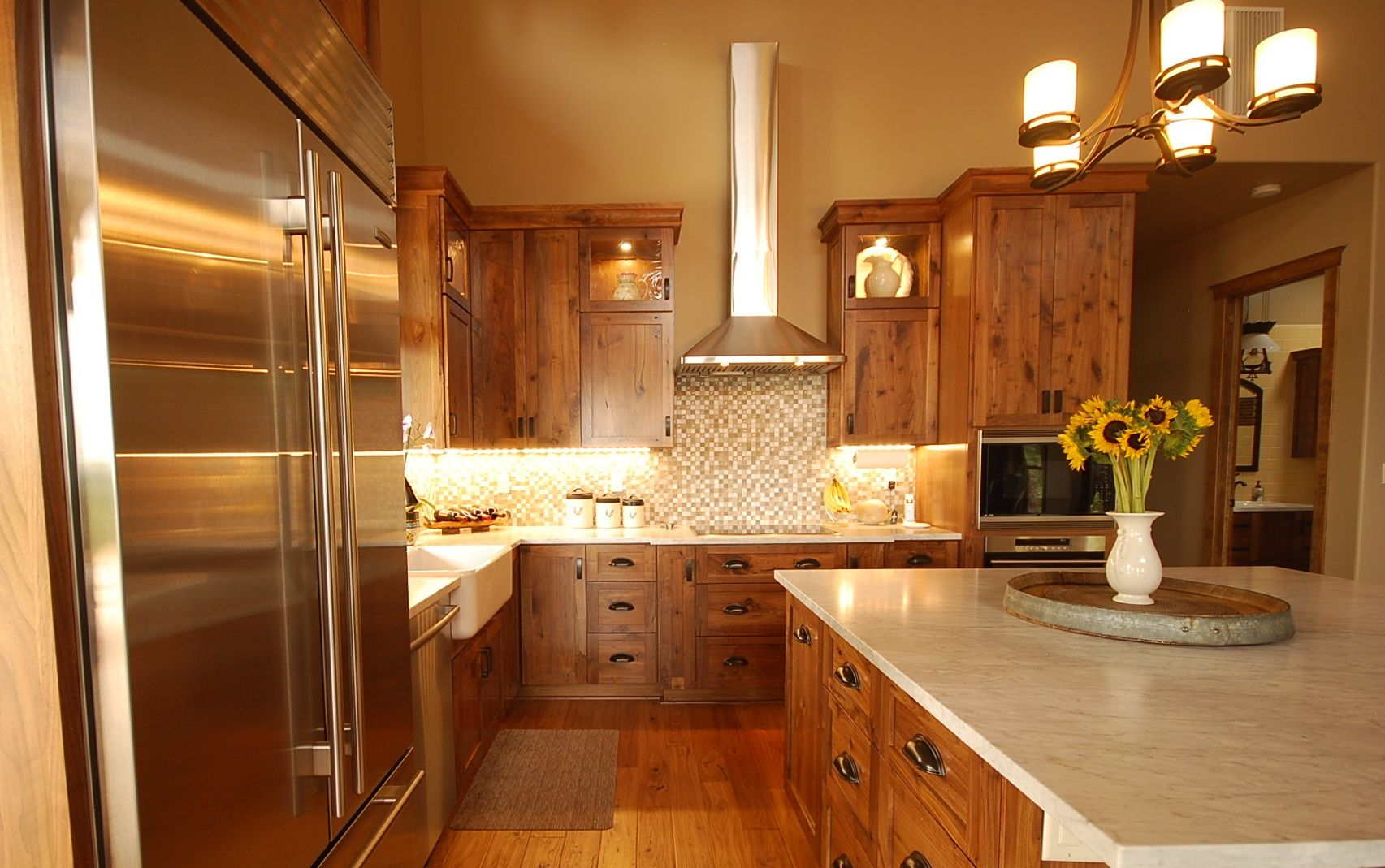 Rustic alder cabinetry, white countertop, stainless steel appliances ...