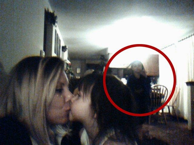 """Real Ghost Pictures: The Morticians Daughter -A friend of mine was taking a picture of herself and her daughter kissing and in the background you can clearly see a figure that was not there. She had """"ghost experts"""" come in and check around the house and found nothing. After some research they found one of the previous owners was a mortician or ran a funeral home or something. I have known this girl for years and it would completely shock me if this was fabricated as I saw how upset she was."""