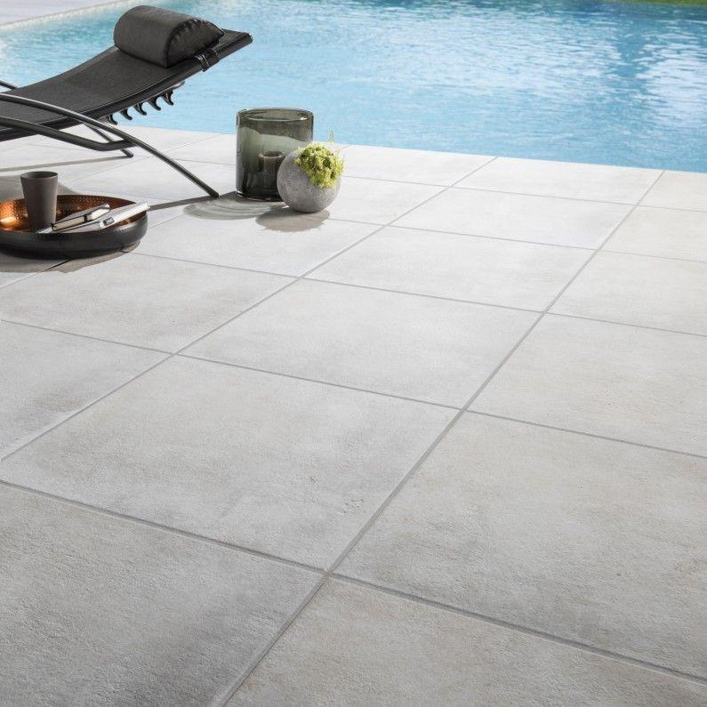 Des carreaux de carrelage effet pierre aux abords de la piscine - pose carrelage terrasse sur dalle beton
