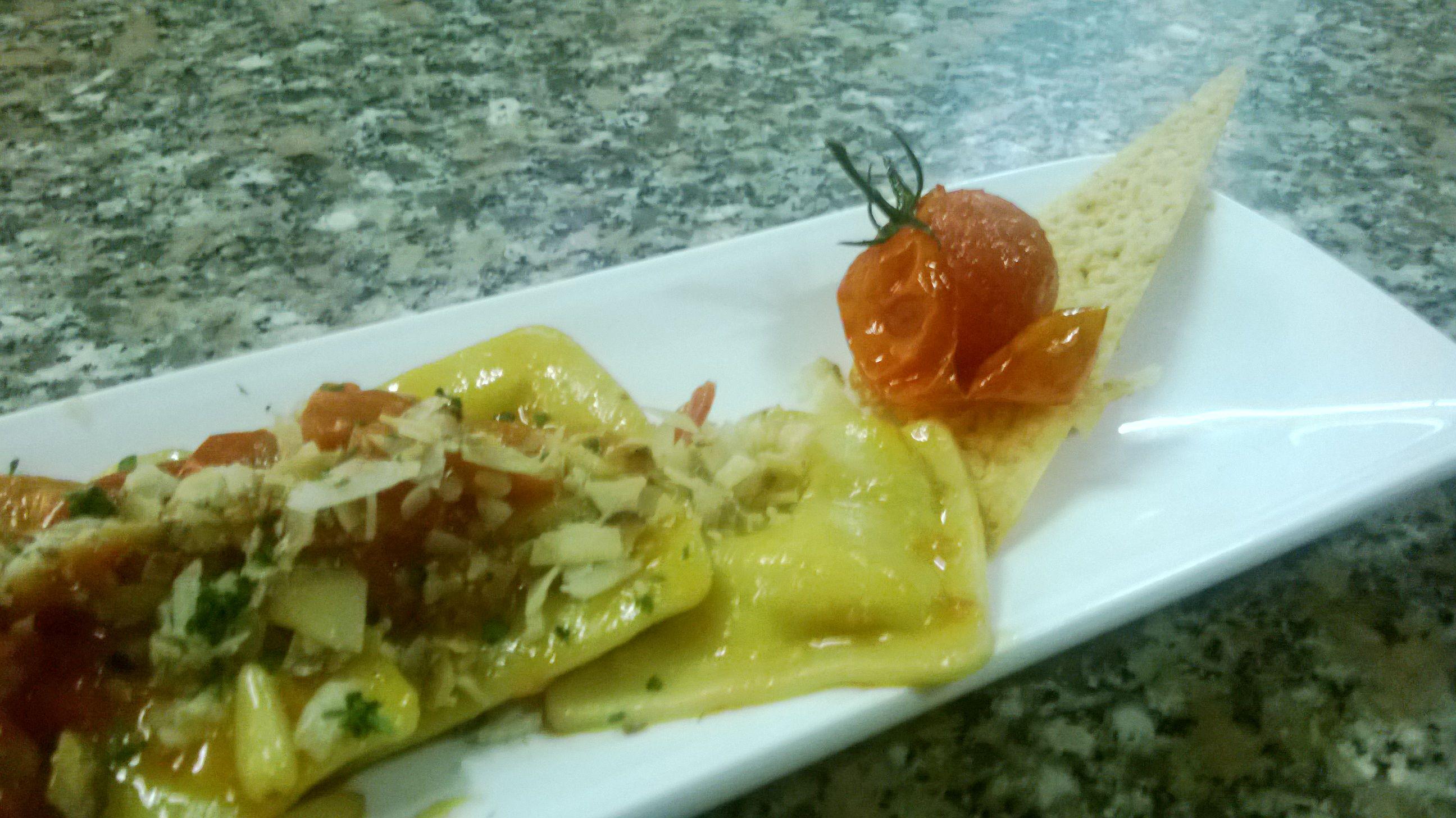 Ravioli di carciofi con pomodorini, pinoli e ricotta affumicata. Pasta filled with artichokes, cherry tomatoes, seasoned cheese and pinenuts