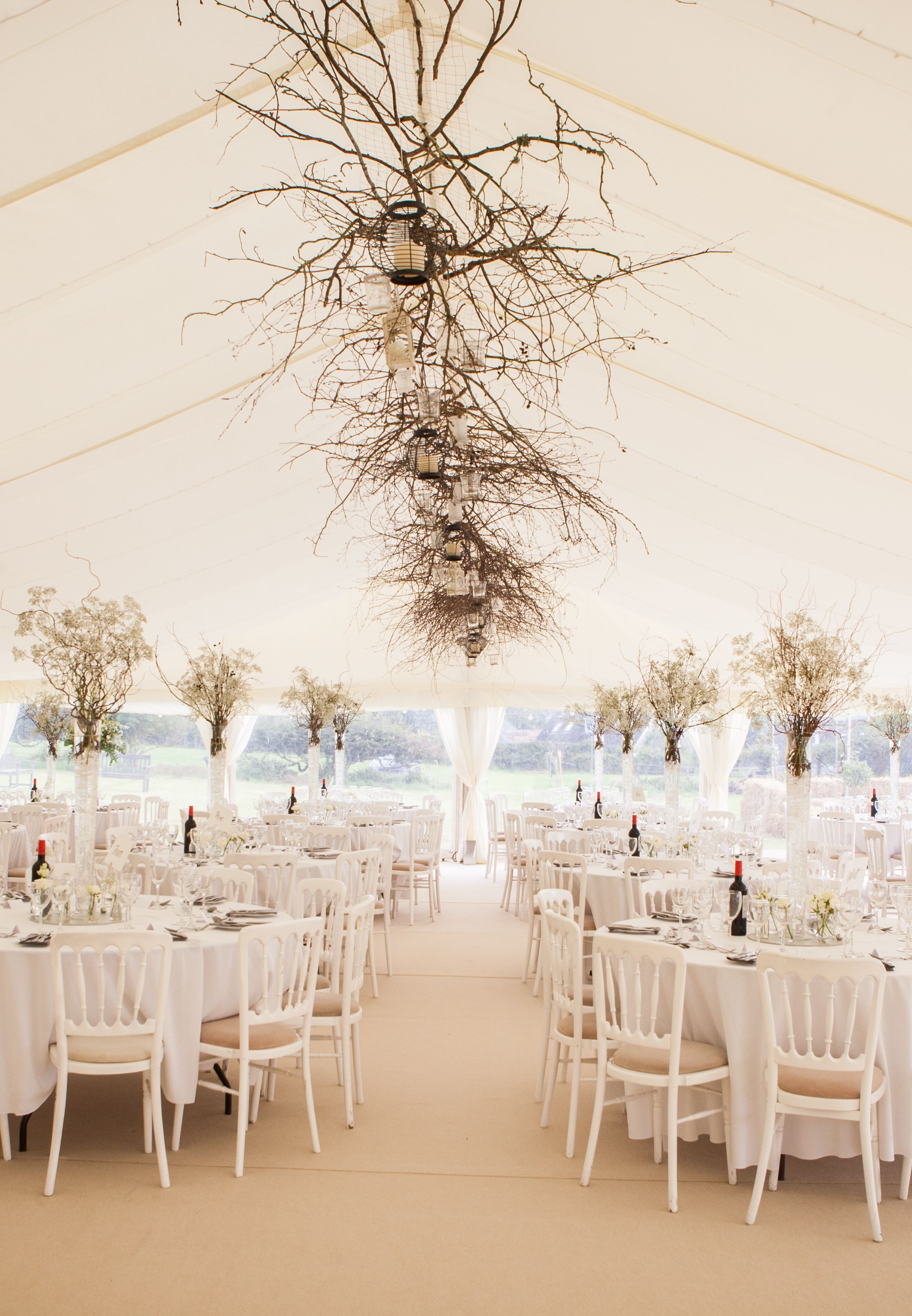 Stylish wedding marquee Fairy lights behind the flat linings twigs