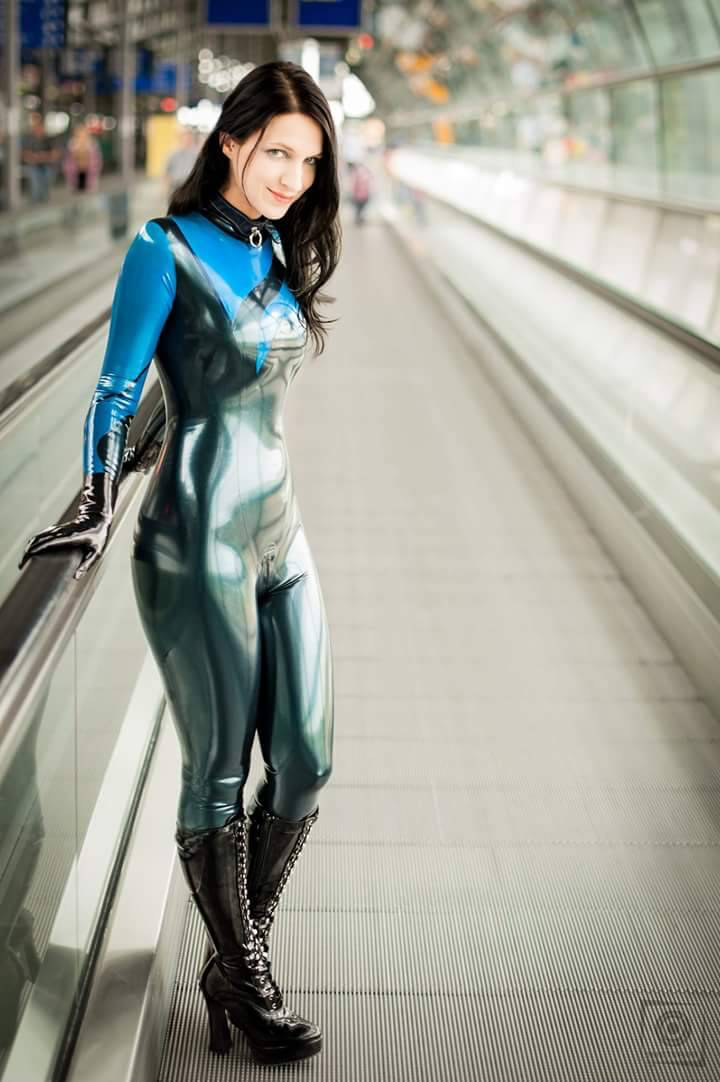Woman in blue and black casual latex catsuit in public airport or train station