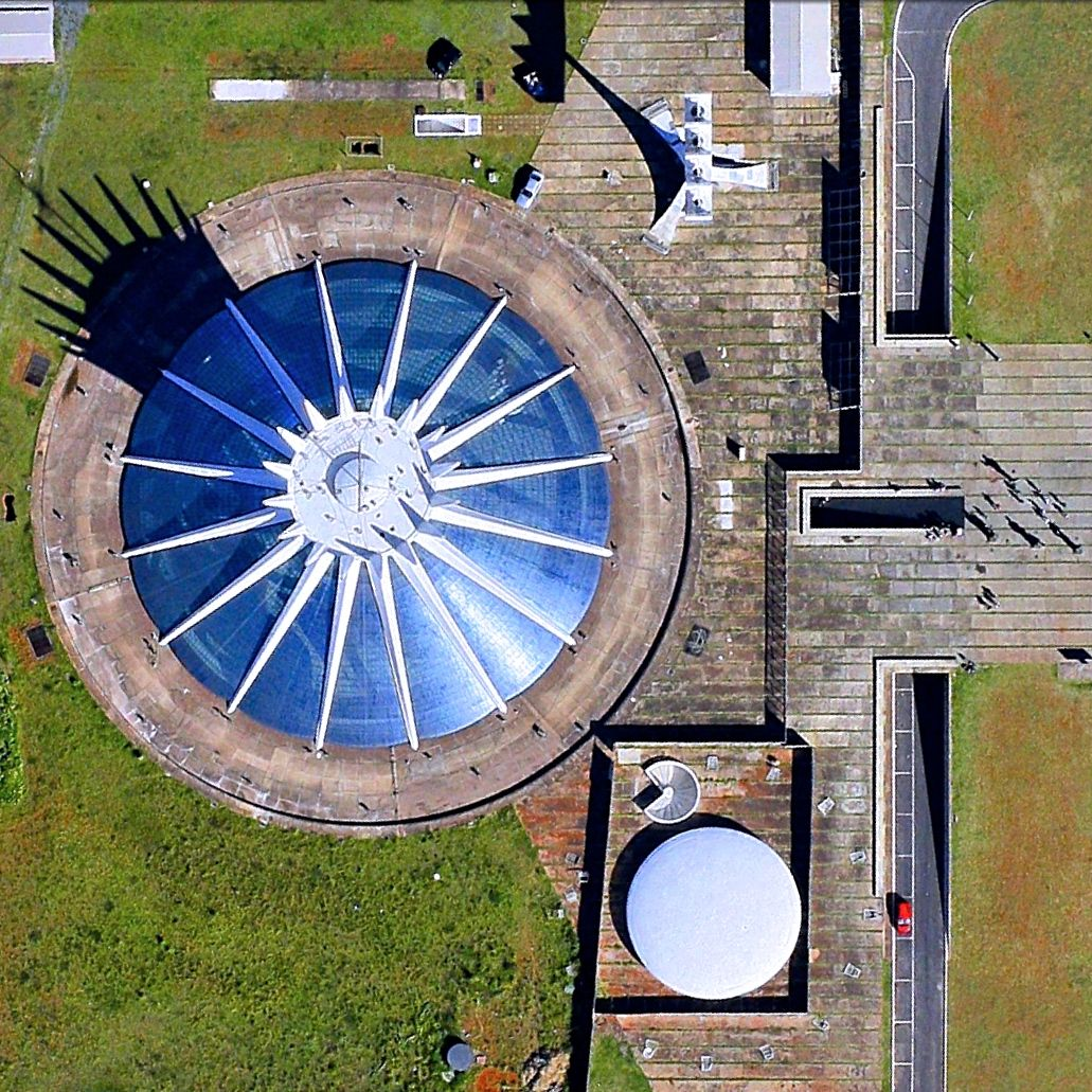 4/5/2015 Cathedral of Brasília Brasília, Brazil -15.798308764°, -47.875430787°   Happy Easter from Daily Overview! The Cathedral of Brasília is the Roman Catholic church that serves the Brazilian capital city and hosts more than 1 million visitors each year. Designed by Oscar Niemeyer, the cathedral is a hyperboloid structure, constructed from 16 concrete columns, that weigh 90 tons each and cast the crown-like shadow that we see here.