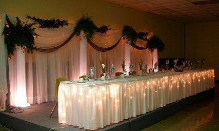 With Lighted Bases, Greenery And Lights. Head Table: White Linen, Table  Skirting