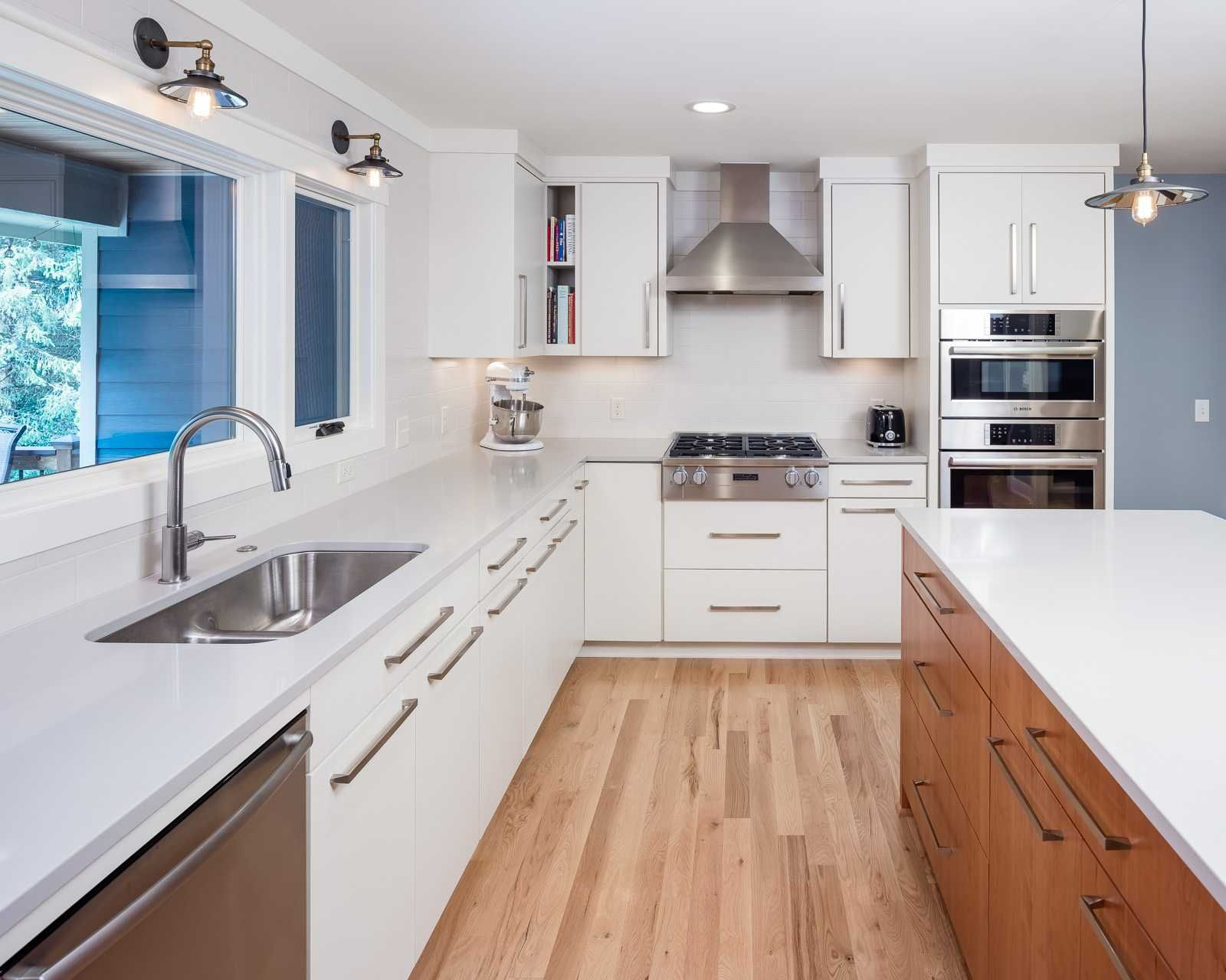 Modern kitchen with white cabinets, a cherry wood island ...