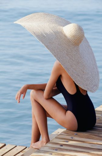 Woman In Straw Hat Sitting On Pier Stock Photo 200226367-001