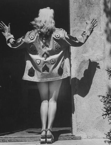Rear view of actress Betty Grable modeling shirt of her own design decorated w. Army insignias while showing off her famous legs in the process. Hollywood, CA, June 1943