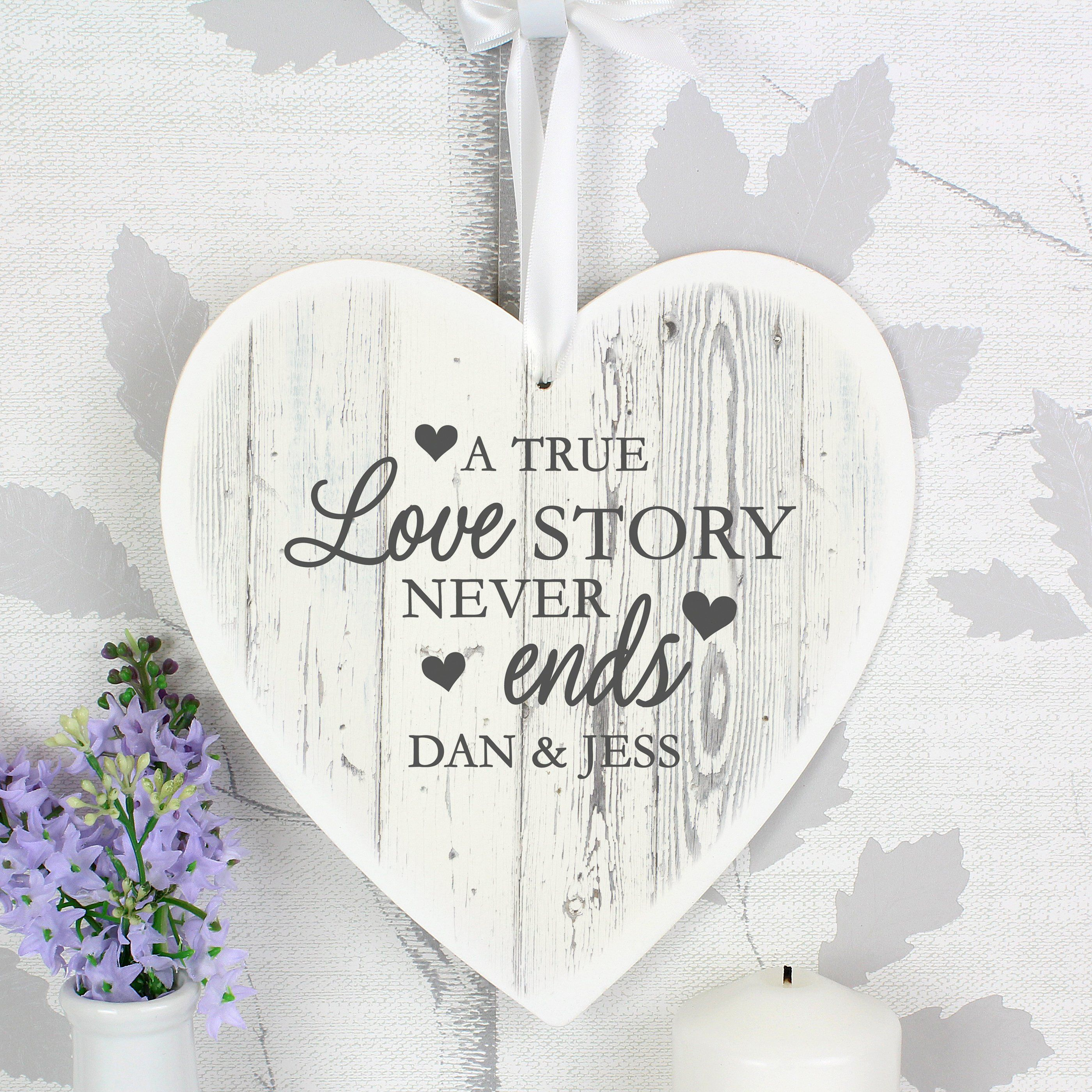 This stunning Personalised Love Story 22cm Large Wooden Heart Decoration is a perfect way to add a romantic touch to your home. This wooden heart decoration can be personalised with a line of text of up to 25 characters The text will appear in fixed upper case. The words 'A true love story never ends' are fixed and cannot be amended. This item is supplied with ribbon ready to hang onto a gift, mantelpiece or tree. Ideal for Weddings, Valentine's Day, Anniversaries and New Home.