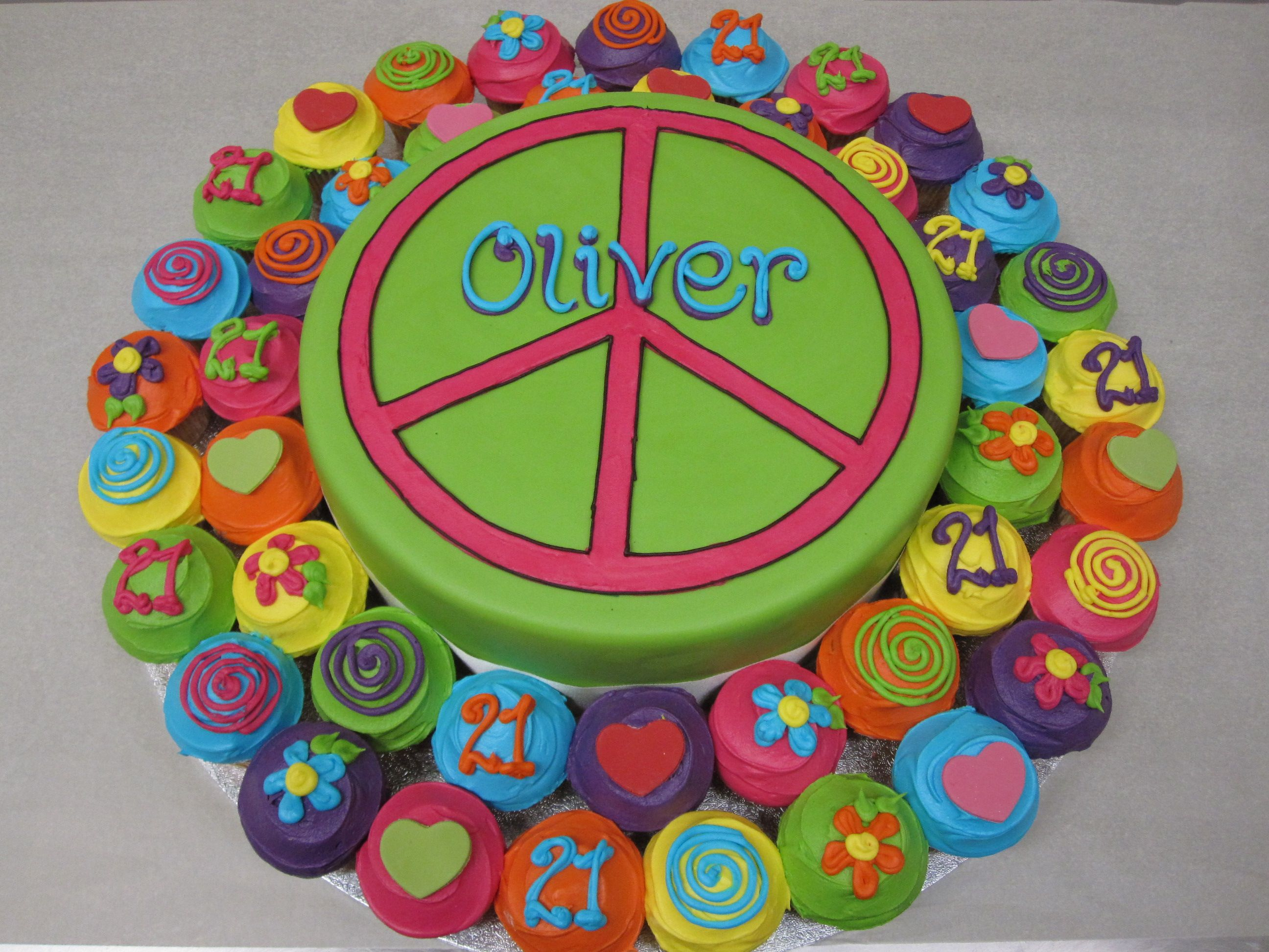 Flower Power Hippie Style Arrangement With Cutting Cake In The Middle And Mini Cupcakes Around