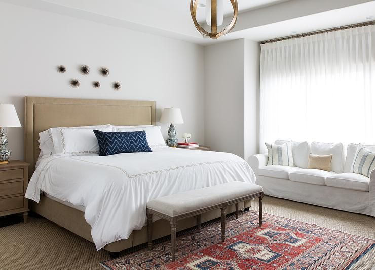 Restful white and beige transitional bedroom features windows ...