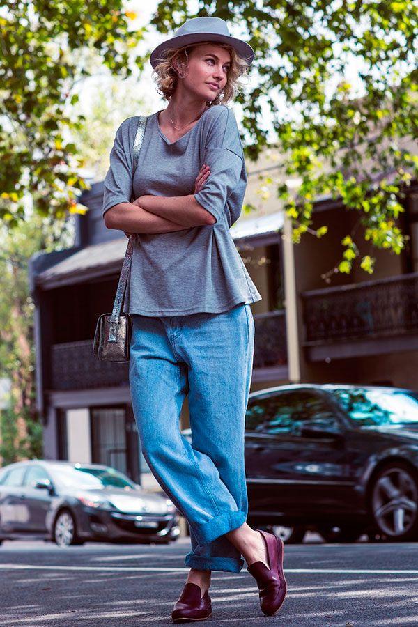 Street style look com calça jeans modelo boyfriend, mocassim burgundy, blusa manga longa cinza, bolsa prata metalizada e chapéu cinza.