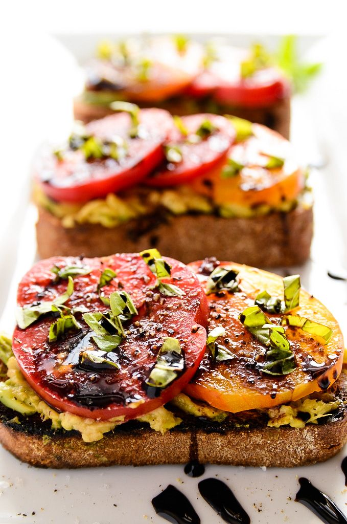 Avocado + Heirloom Tomato Toast with Balsamic Drizzle | Toasted bread is slathered with creamy avocado + topped with juicy tomatoes, fresh basil + balsamic!