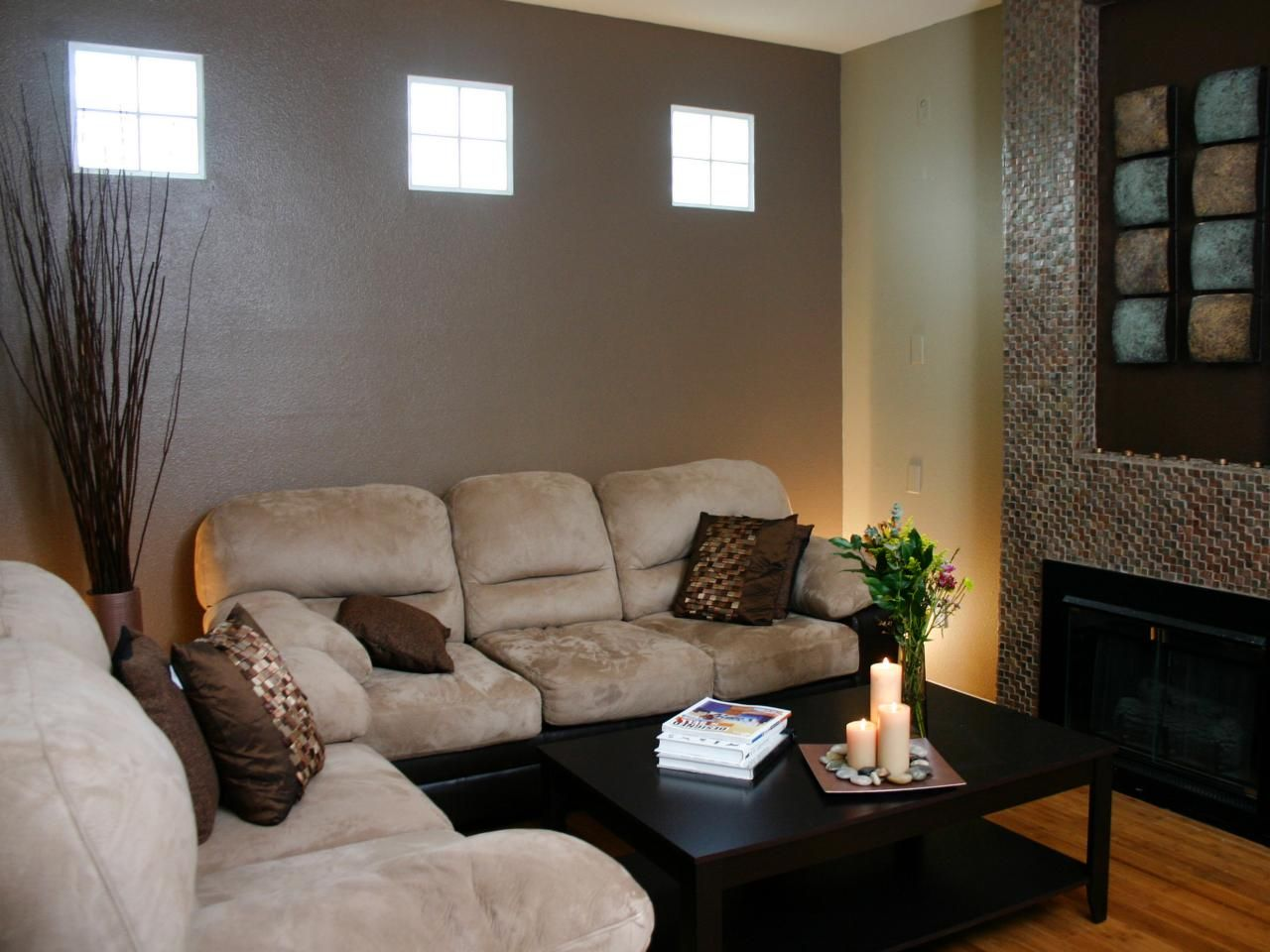 A dramatic fireplace decked in black brown and cream - Brown suede living room furniture ...