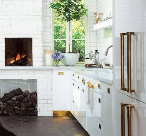 unlacquered brass toe kick and hardware against lacquered cabinets and subway tile.  also love the high fireplace