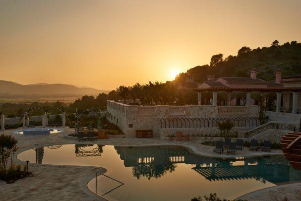 Das Park Hyatt Hotel bei Sonnenuntergang: In einem der beiden Außenpools spiegelt sich das einzigartige Licht Mallorcas. (Foto: Park Hyatt Hotel)