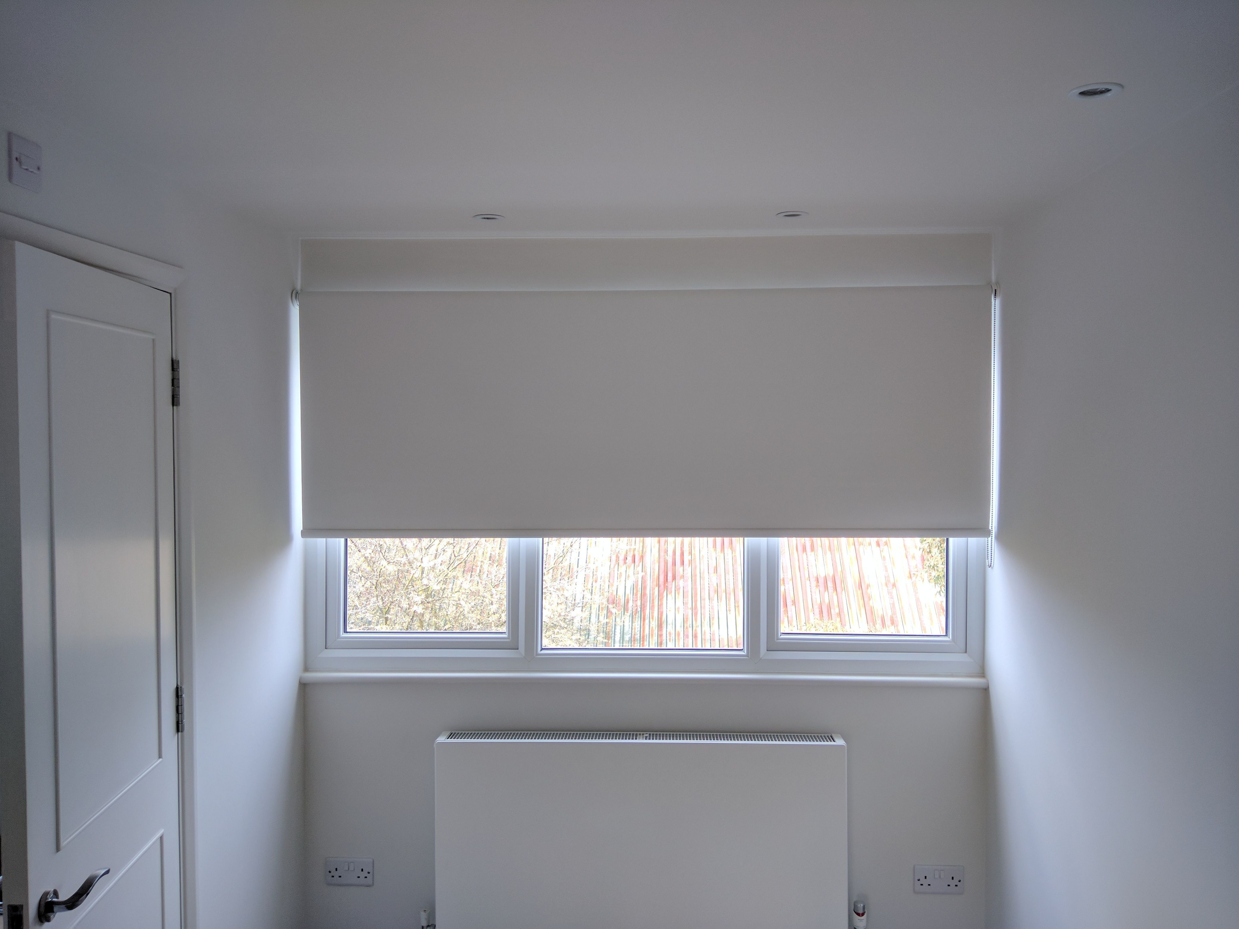 Blackout roller blind in polar white colour fitted to bedroom window