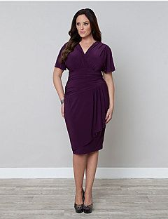 Haute and sultry, our Danika Draped Dress is a beautiful piece with an asymmetrical line at the bottom waist of a fully ruched torso. This becoming silhouette finishes with a faux wrap straight skirt for a slimming effect that includes gathering and a flounce in the front for flirty appeal. Dramatic dolman sleeves flow over the arms in a stylishly feminine way and the surplice neckline adds just the right amount of coverage.