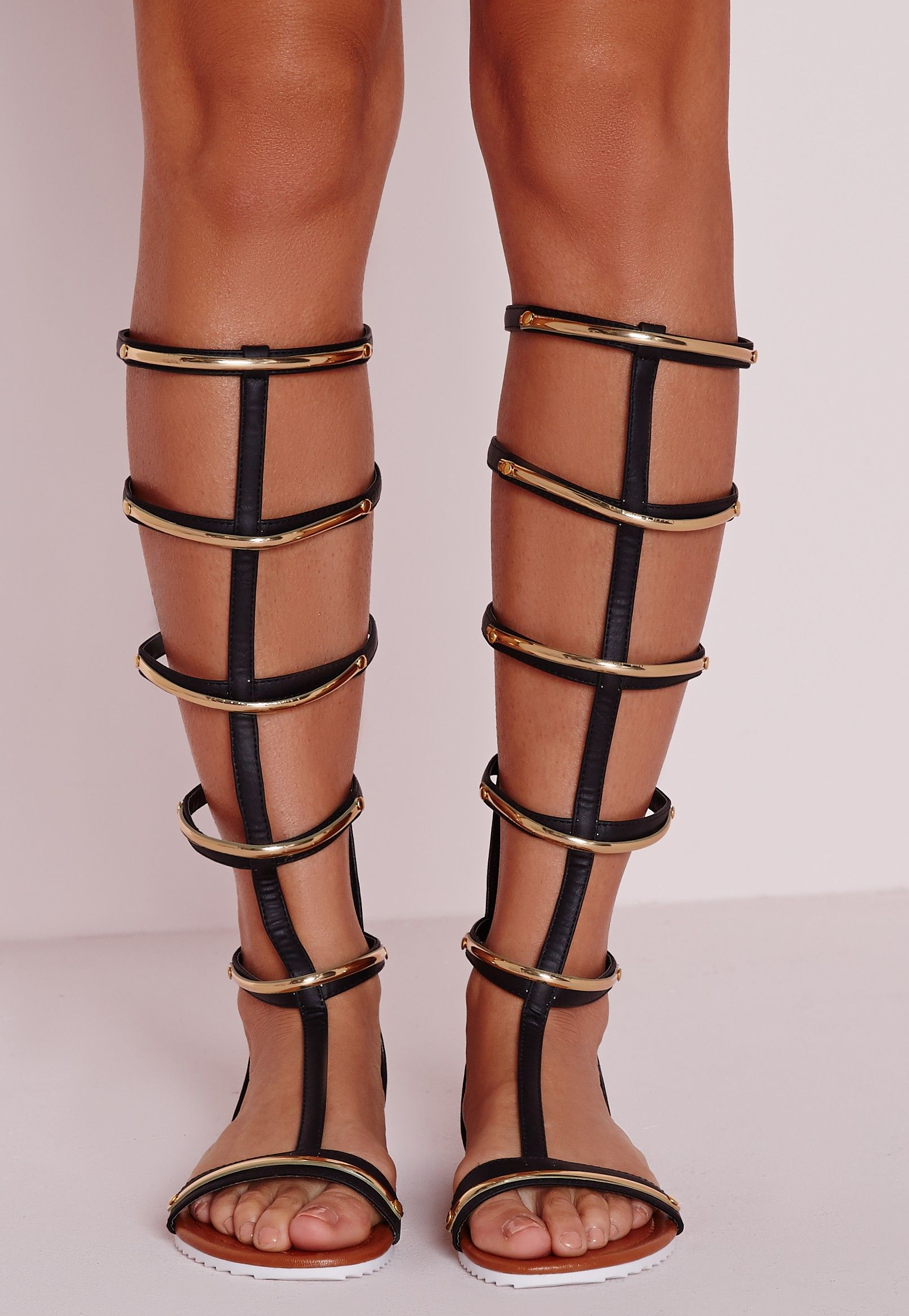 afb3bb9ad11f2a Chanel your inner Greek goddess in these fierce gladiator sandals. In a  black faux leather with gold trim bars these knee high beauts are hot  property.