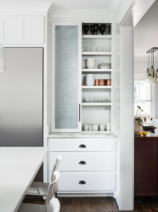 A Stainless Steel Refrigerator Is Inset Beside White Drawers Accented With Matte Black Cup Pulls And Positioned Beneath Shaker Cabinets