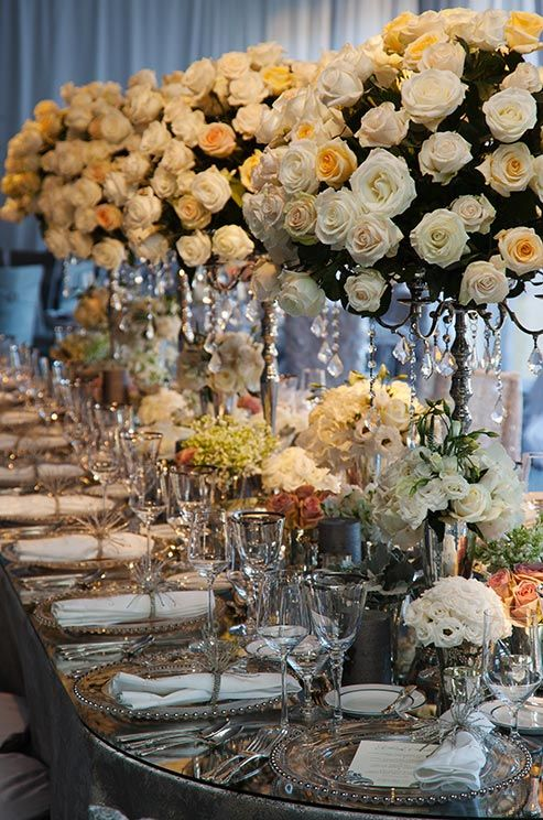 A mirrored table is dressed up with an array of white and soft pink roses and towering centerpieces dripping with crystals.