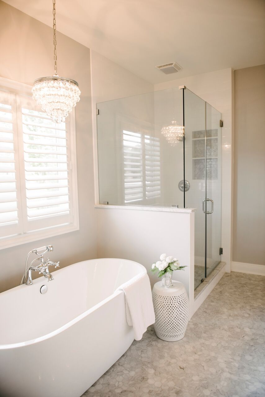 Individual white tub with glamourous light fixture and shower with ...