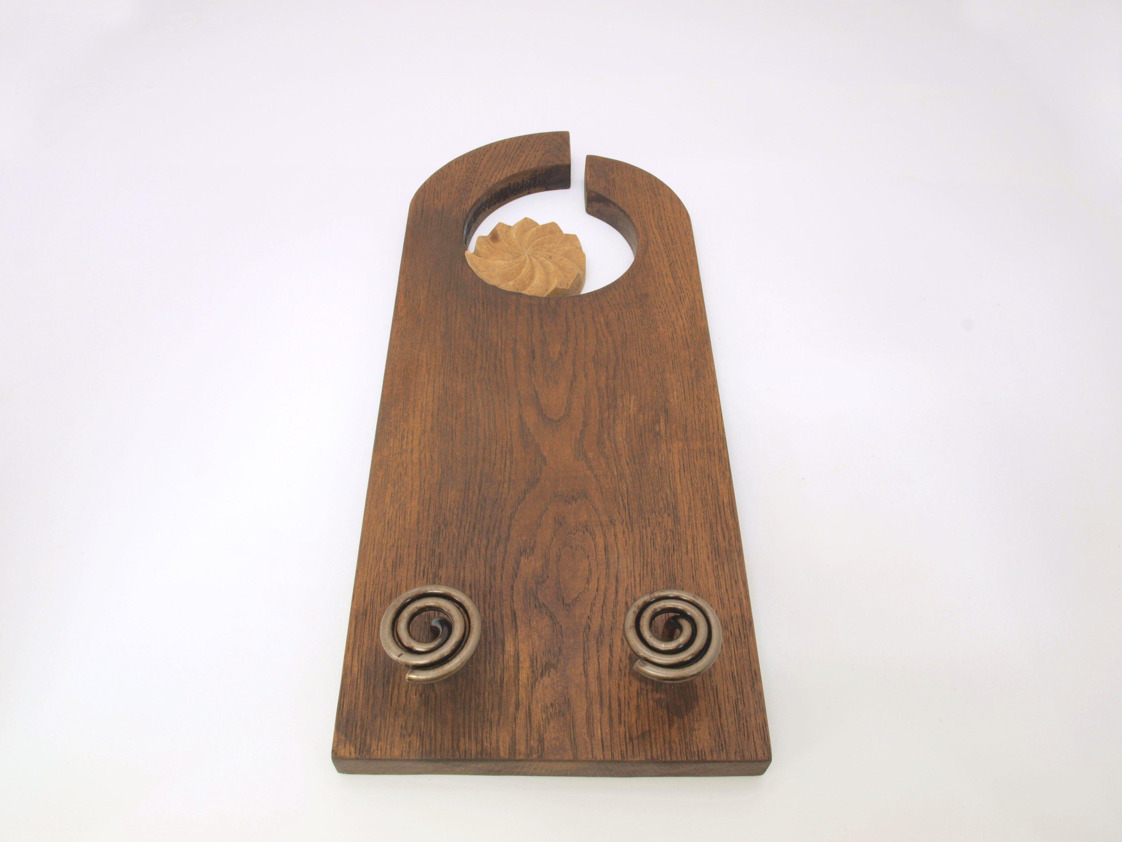 Perchero con estela tallado en madera de roble, tratado con betún judaico a dos tonos con dos perchas de hierro artesanales.  Dimensiones: 60×25cm.aprox.