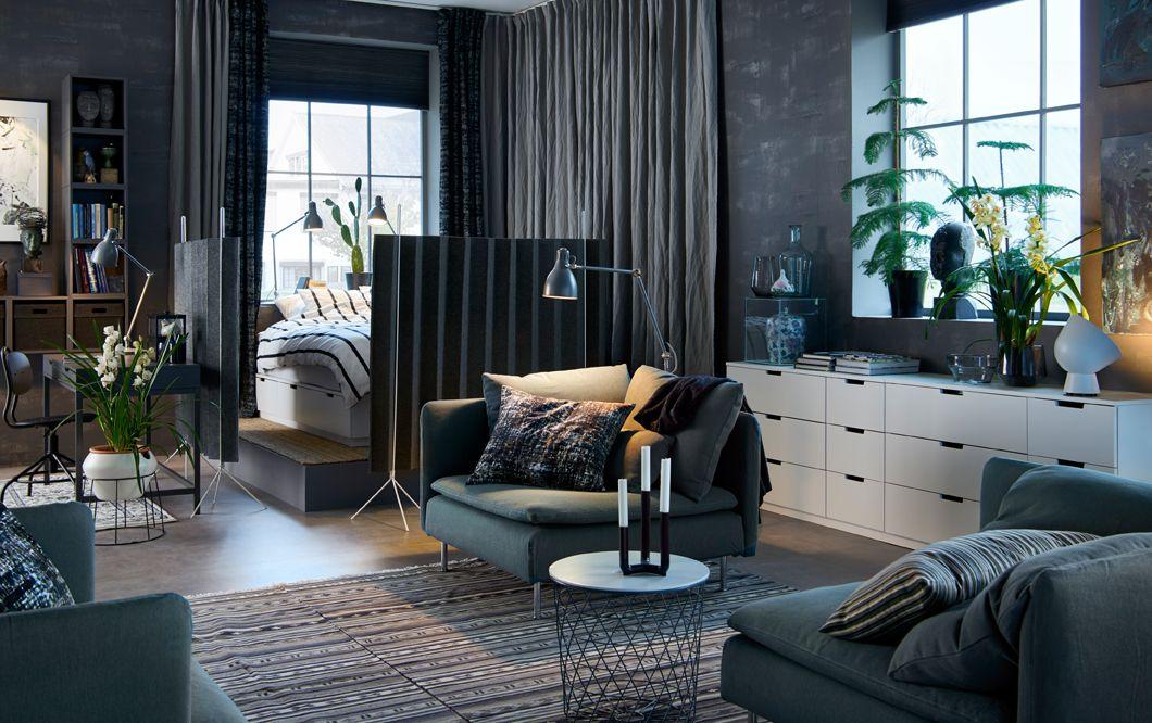 ein offenes studio in dunkelgrau gehalten in einer ecke befindet sich ein schlafbereich der. Black Bedroom Furniture Sets. Home Design Ideas
